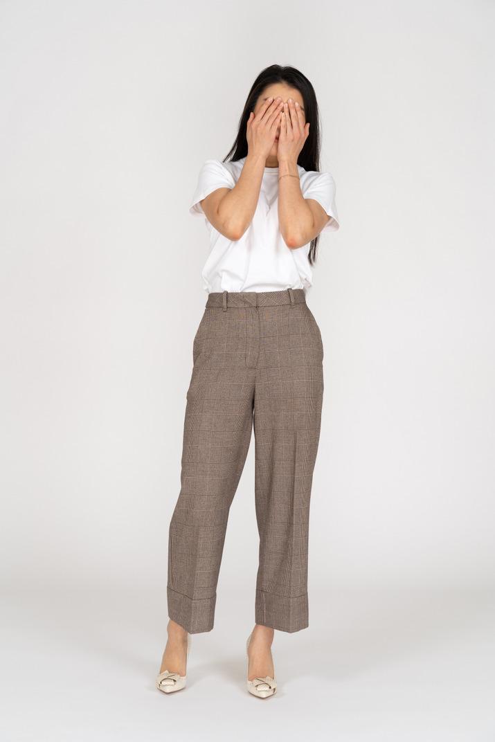Vorderansicht einer jungen dame in reithose und t-shirt, die ihr gesicht versteckt