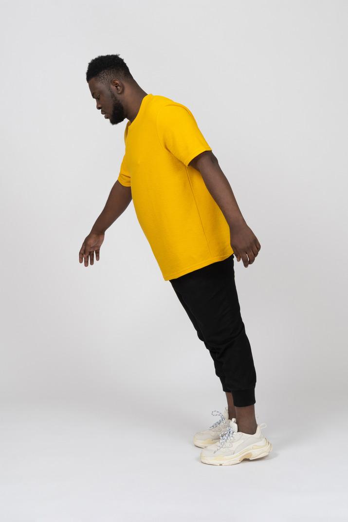 Vue latérale d'un jeune homme à la peau foncée en t-shirt jaune se penchant en avant et bras tendu