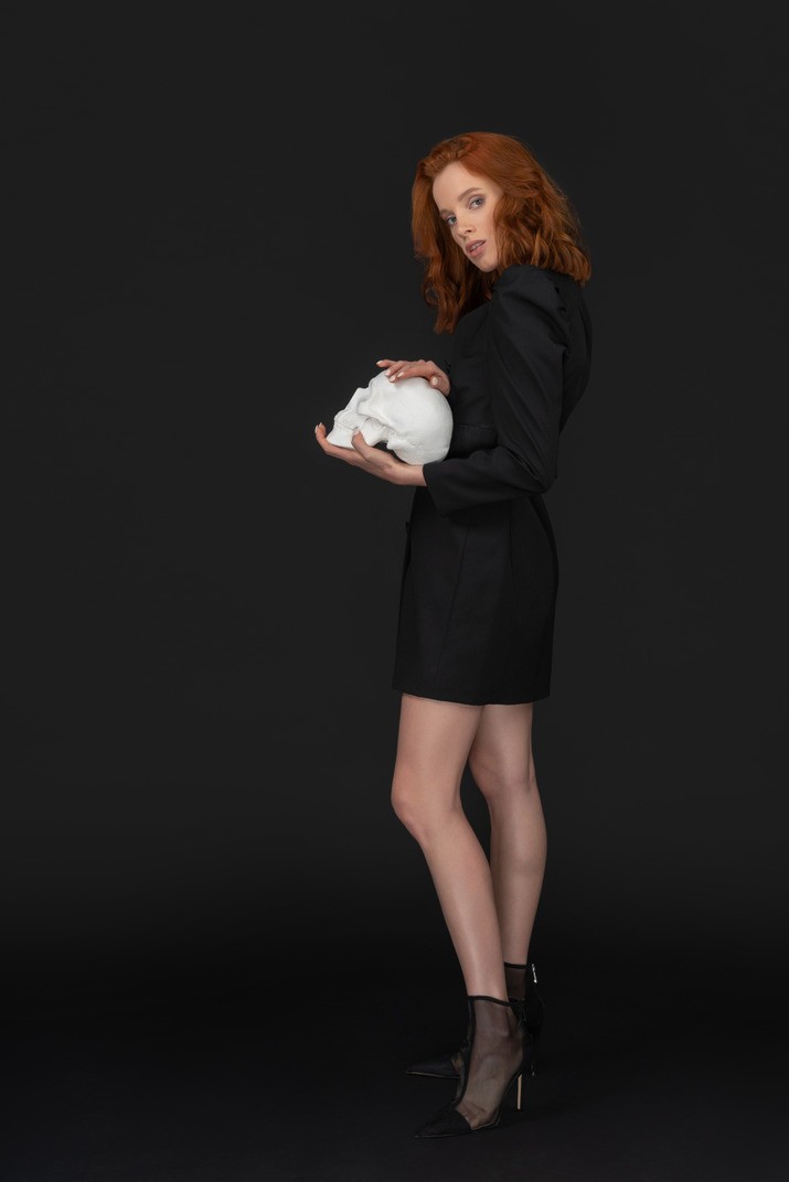 A side view of the cute young woman holding a skull and looking to the camera
