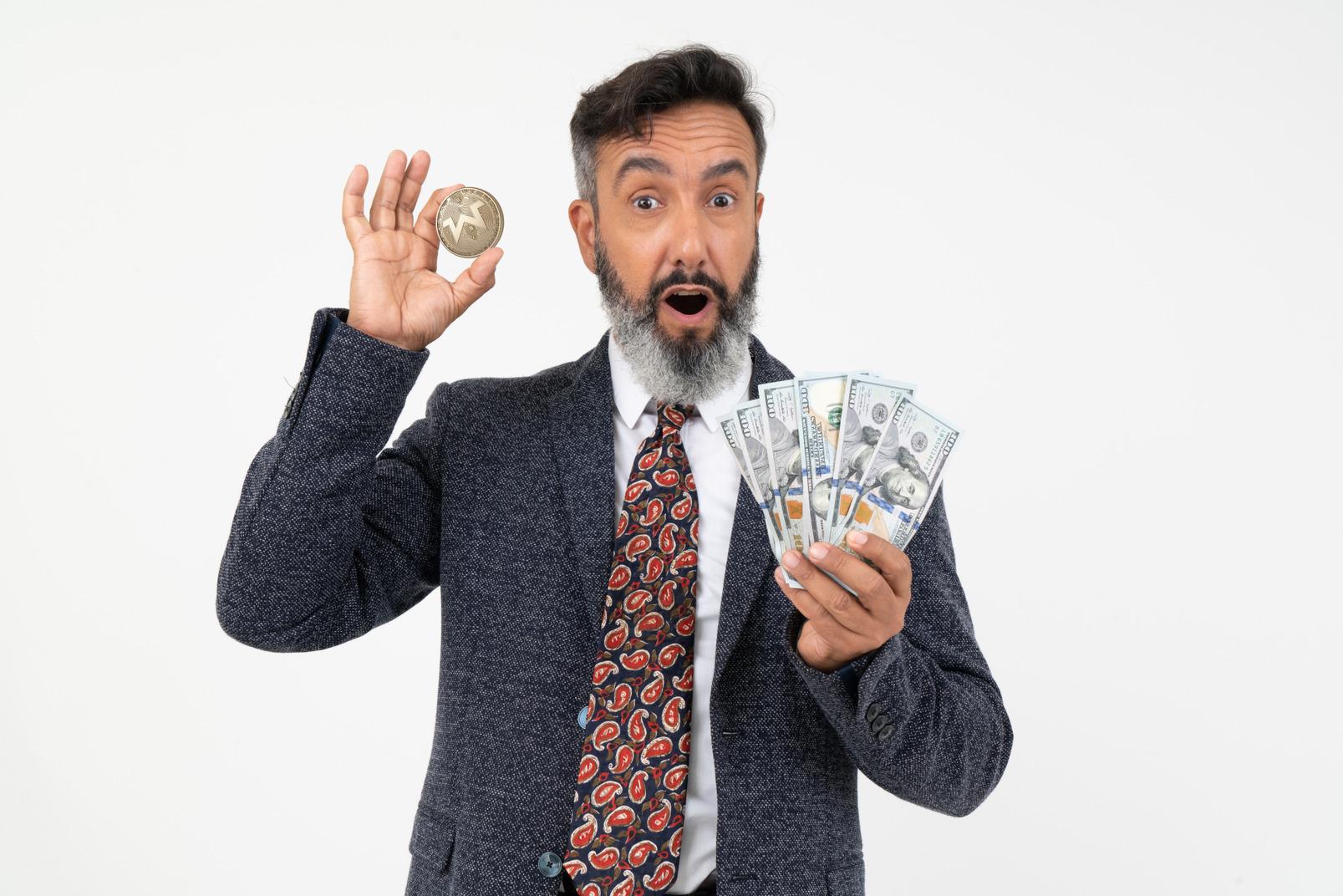 Reifer mann, der eine moneromünze und dollarscheine hält