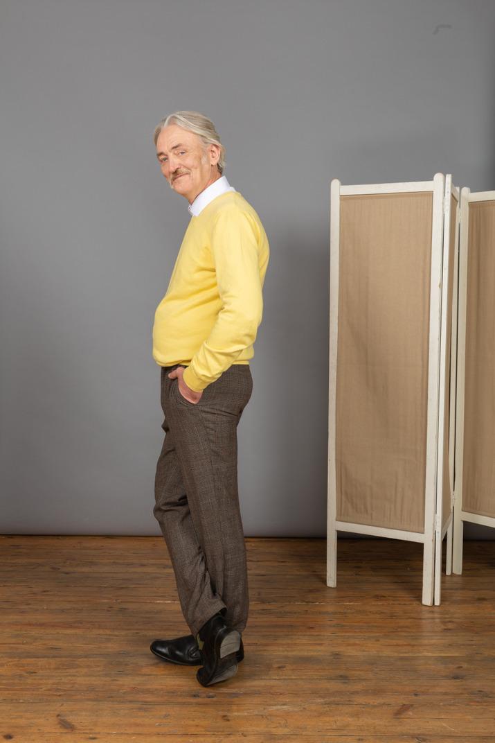 Seitenansicht eines lächelnden alten mannes, der hand in tasche steckt, während kamera betrachtet