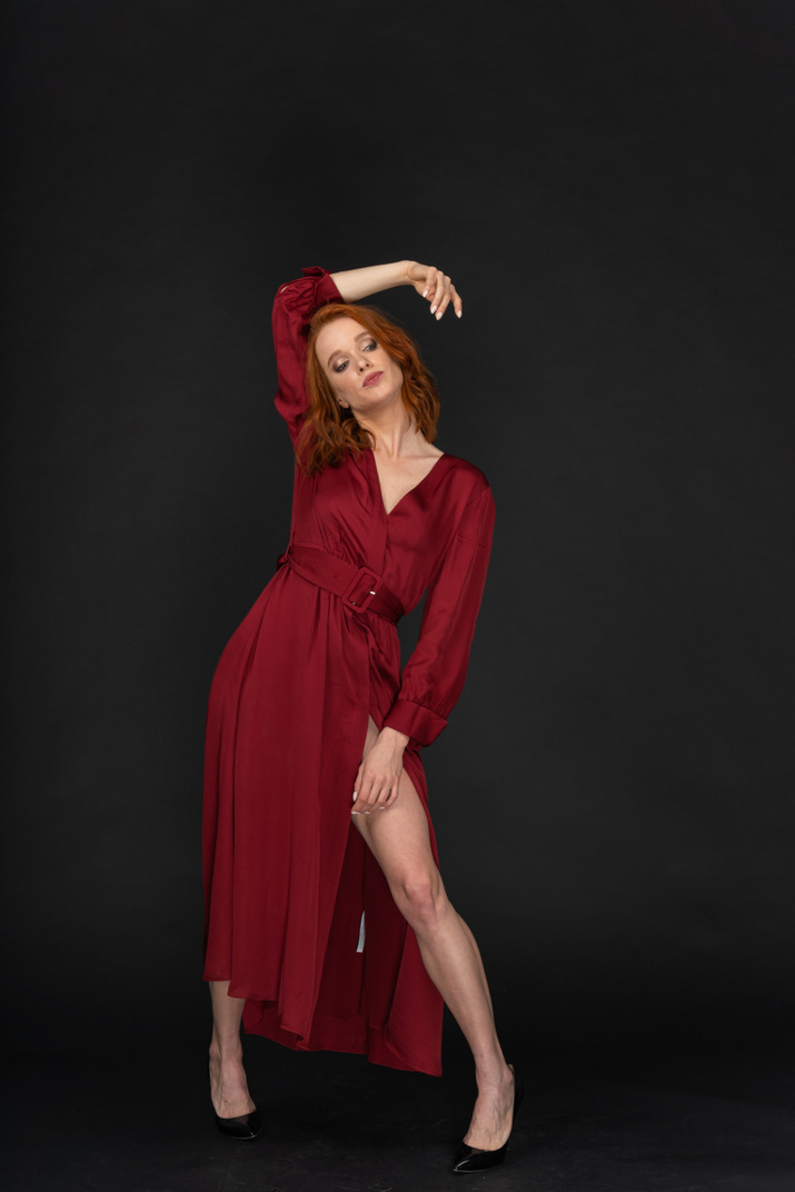 A frontal view of the young woman dressed in red and posing on the black background