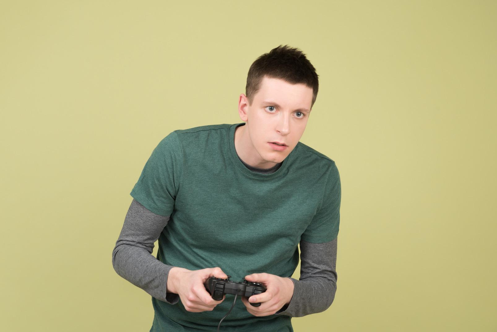 Junger mann, der den gamecontroller spielt videospiele hält