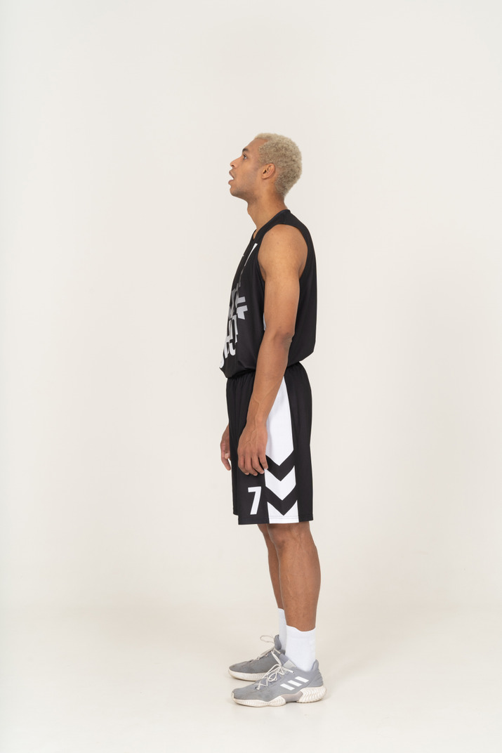 Side view of a gasping young male basketball player