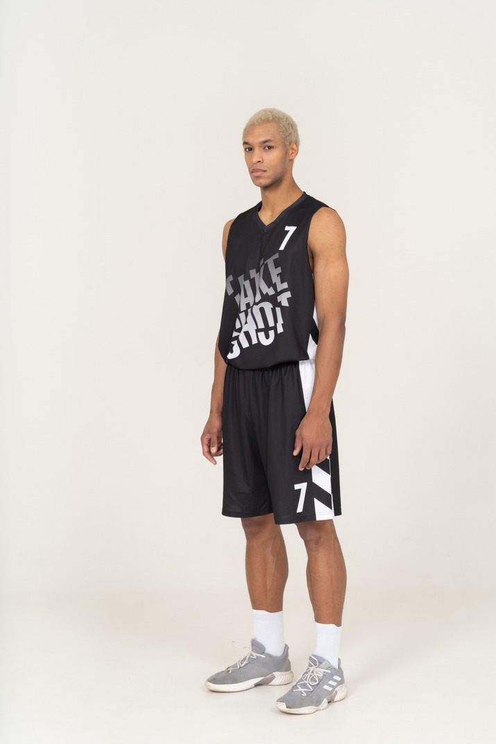 Three-quarter view of a young male basketball player standing still & looking at camera