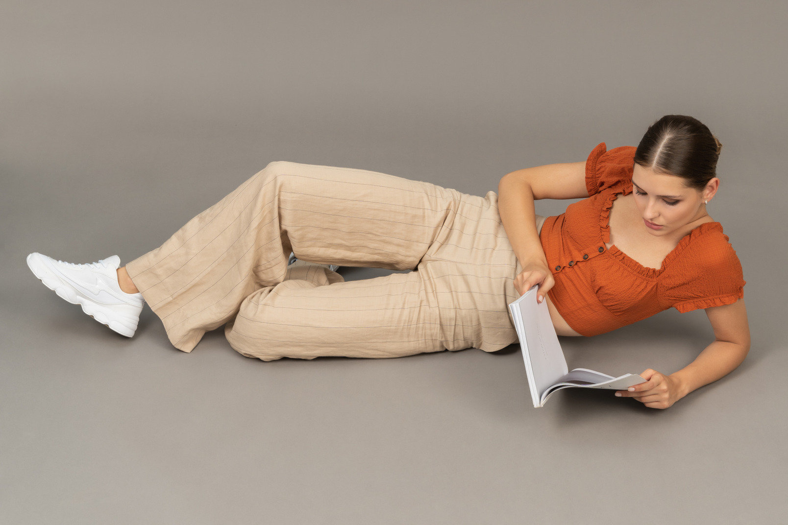 Young woman lying down with book