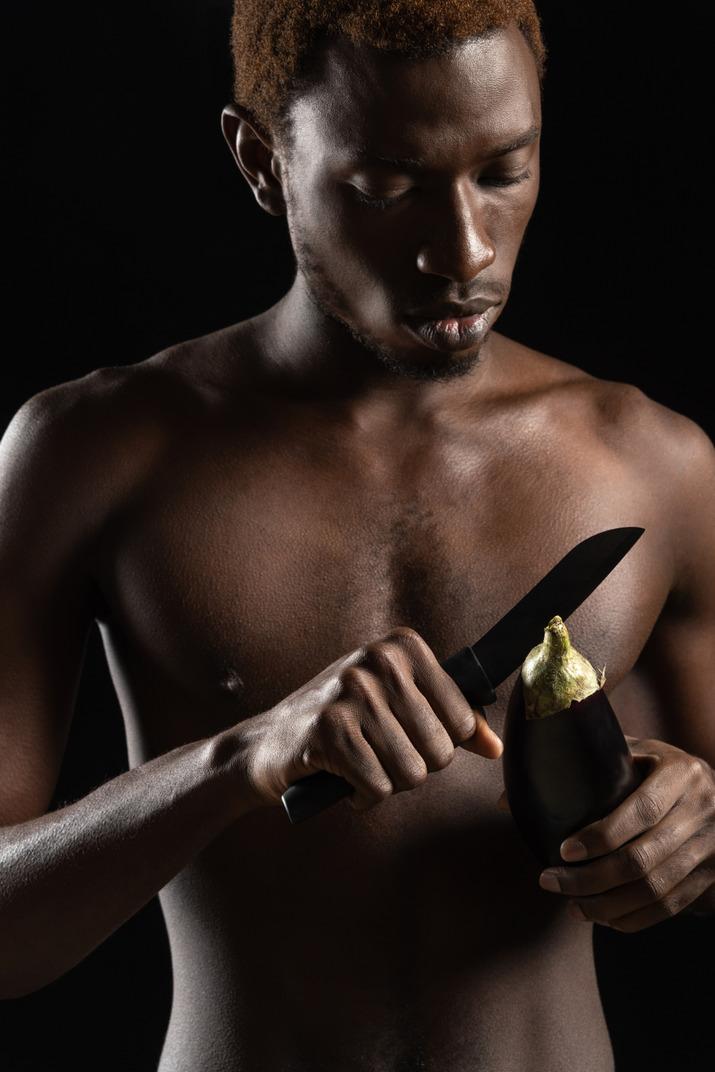 Nahaufnahme eines nackten jungen mannes, der eine aubergine schneidet