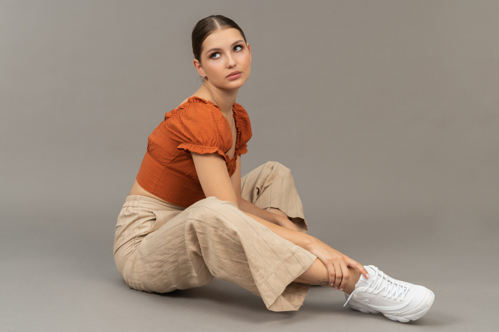 Young woman sits while holding her leg