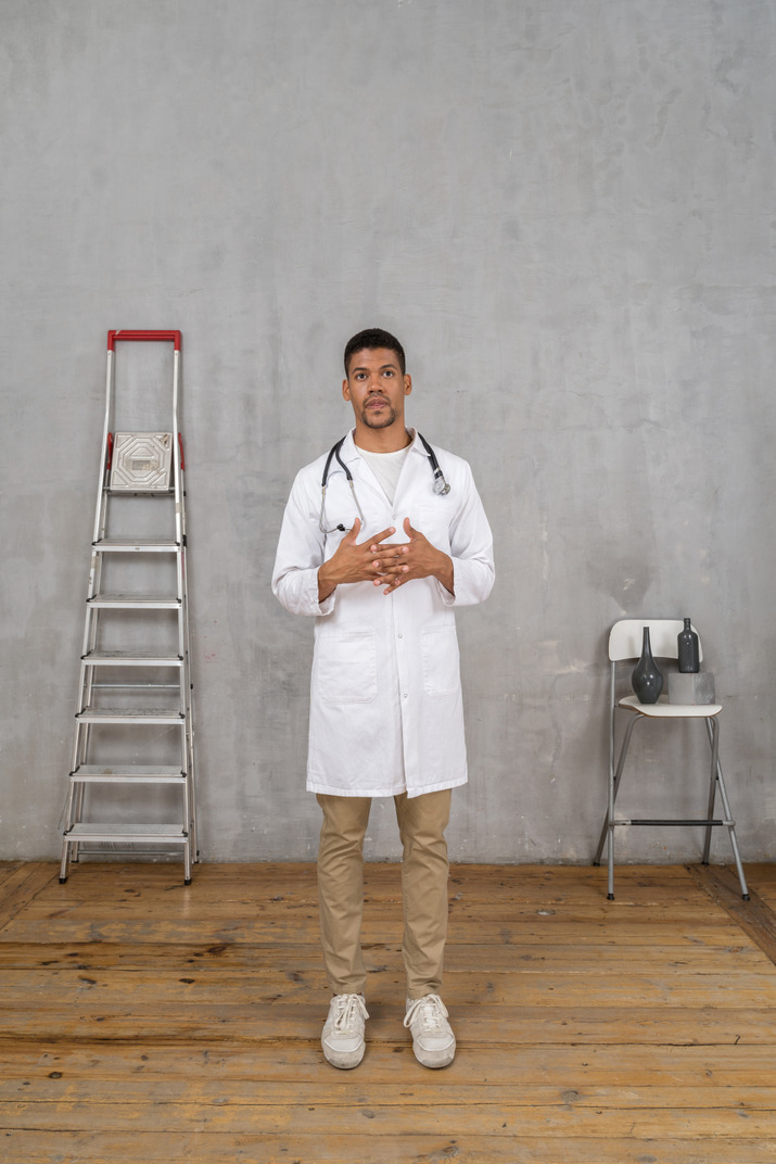 Front view of a young doctor standing in a room with ladder and chair