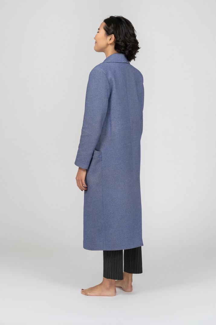 Young woman in long blue coat standing half sideways back to camera