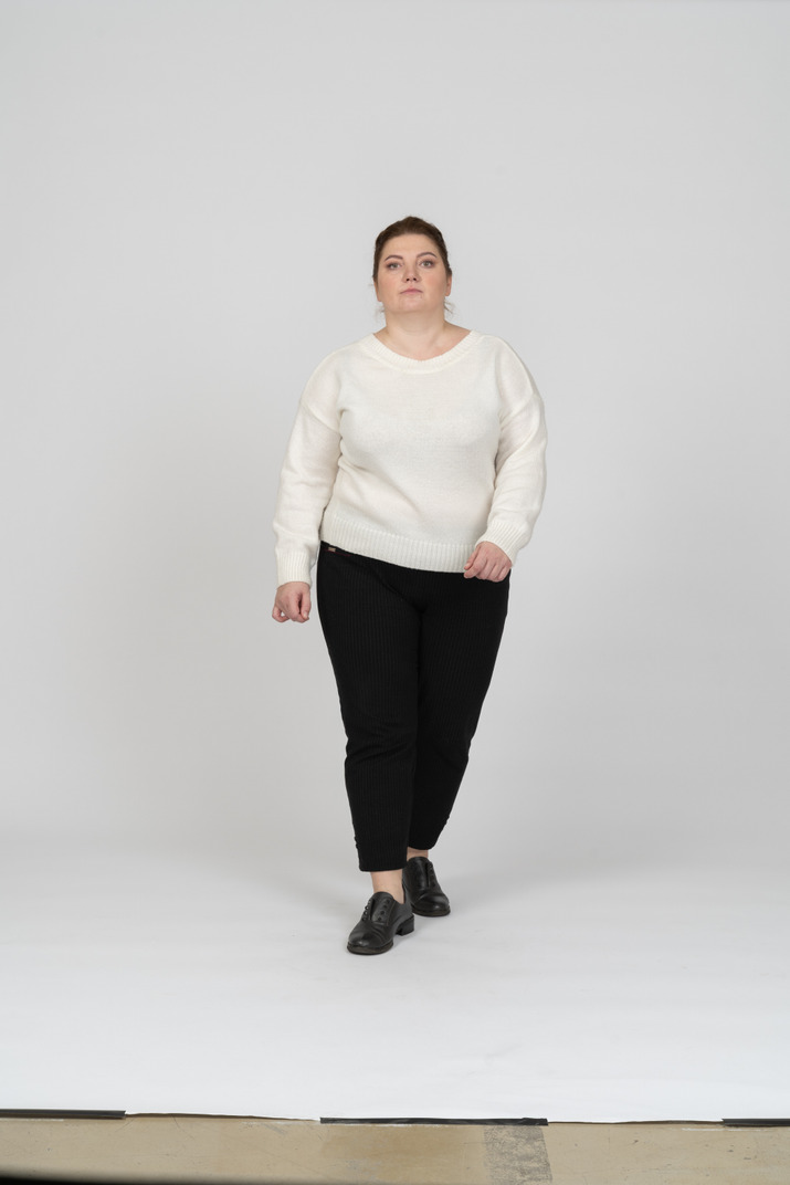 Front view of a plump woman in casual clothes looking at camera