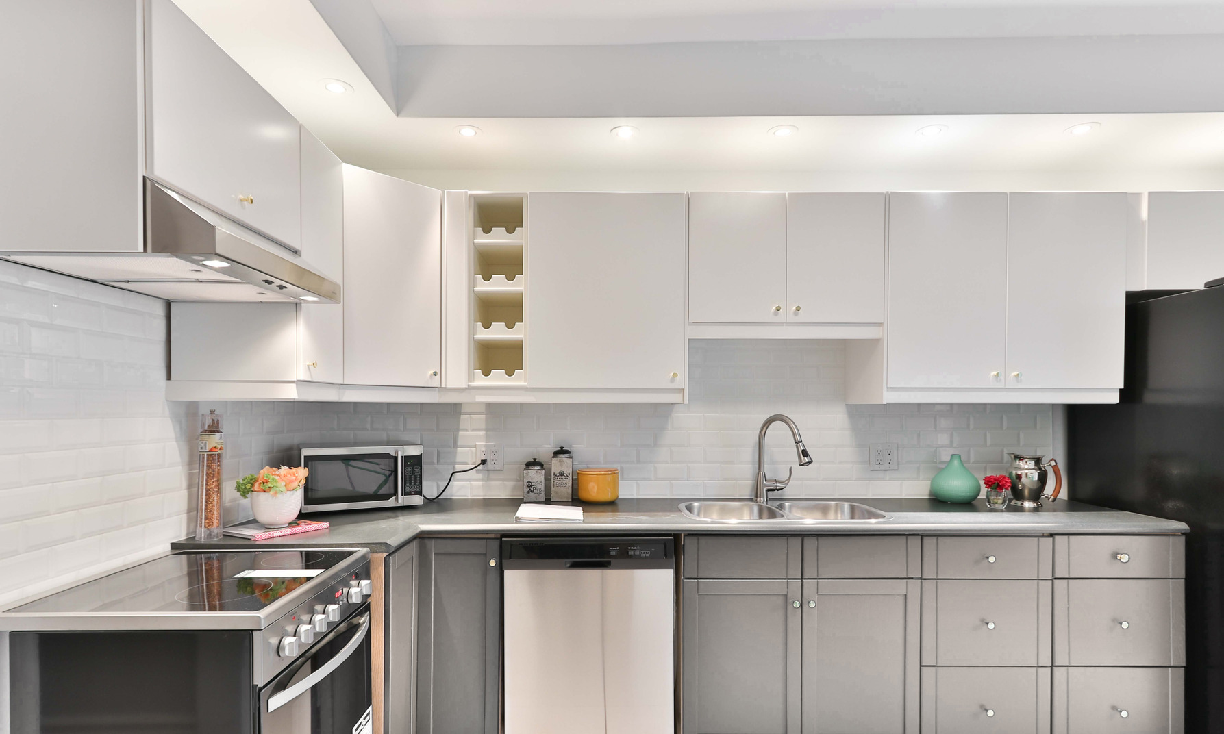 A generic modern kitchen with appliances, cupboards and some decor pieces lit by a row of little lamps