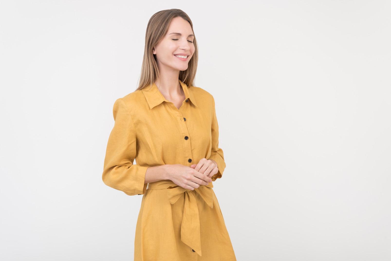 Smiling young caucasian woman in yellow dress