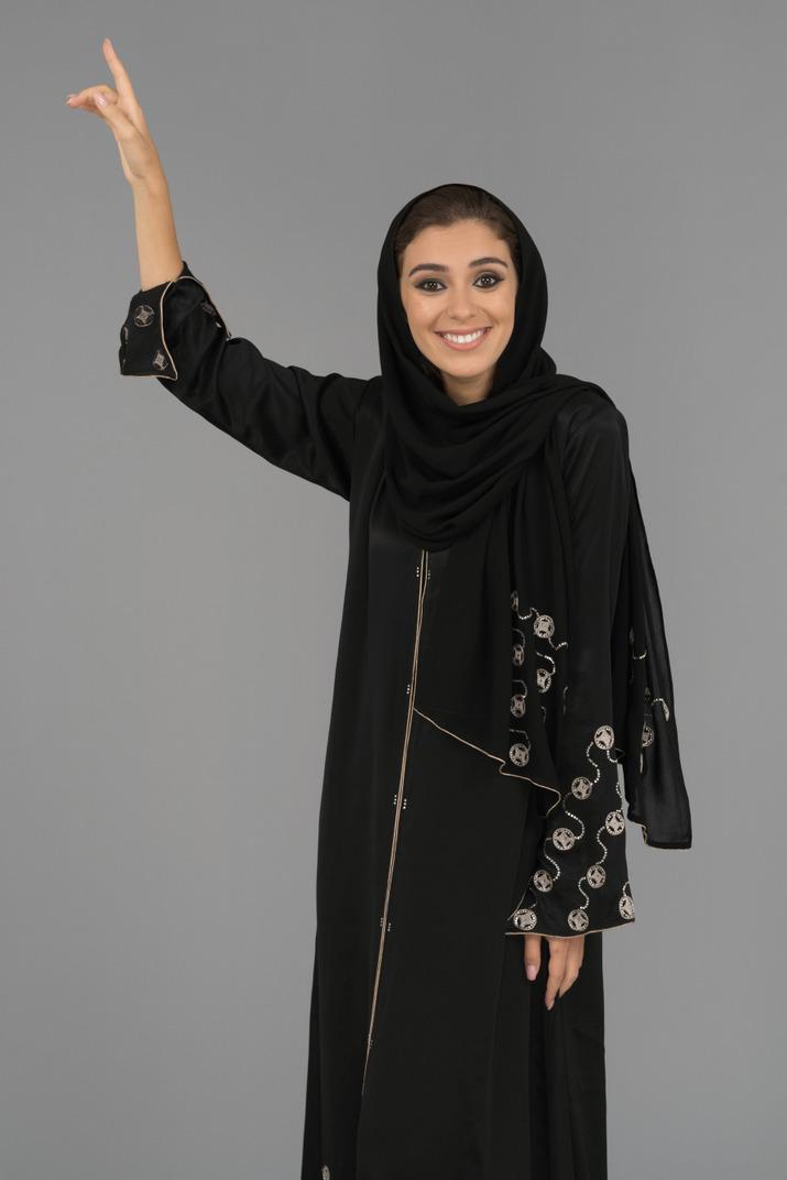 Eine lächelnde muslimische frau, die nach oben zeigt