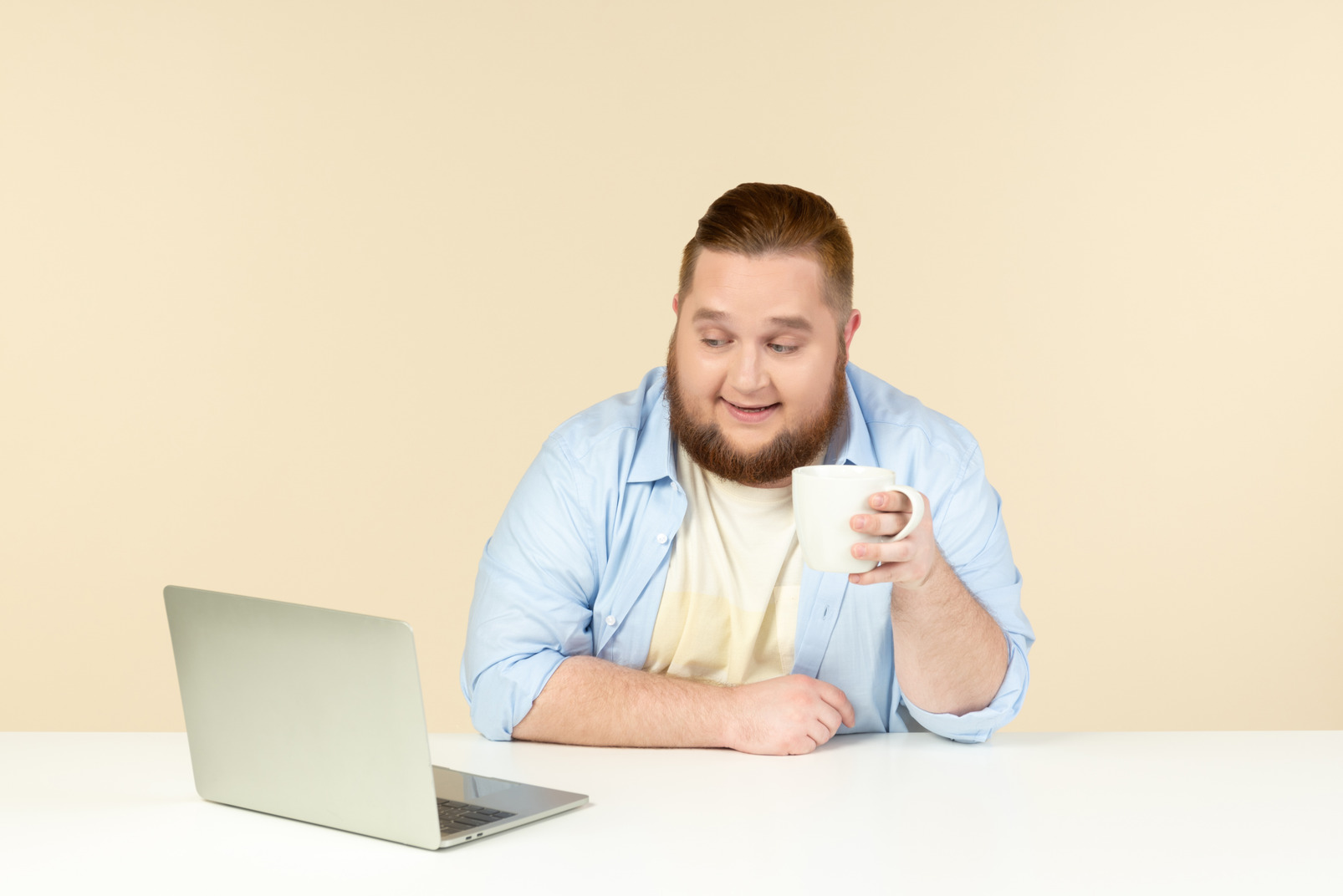 Young overweight man sitting in front of laptop and having tea