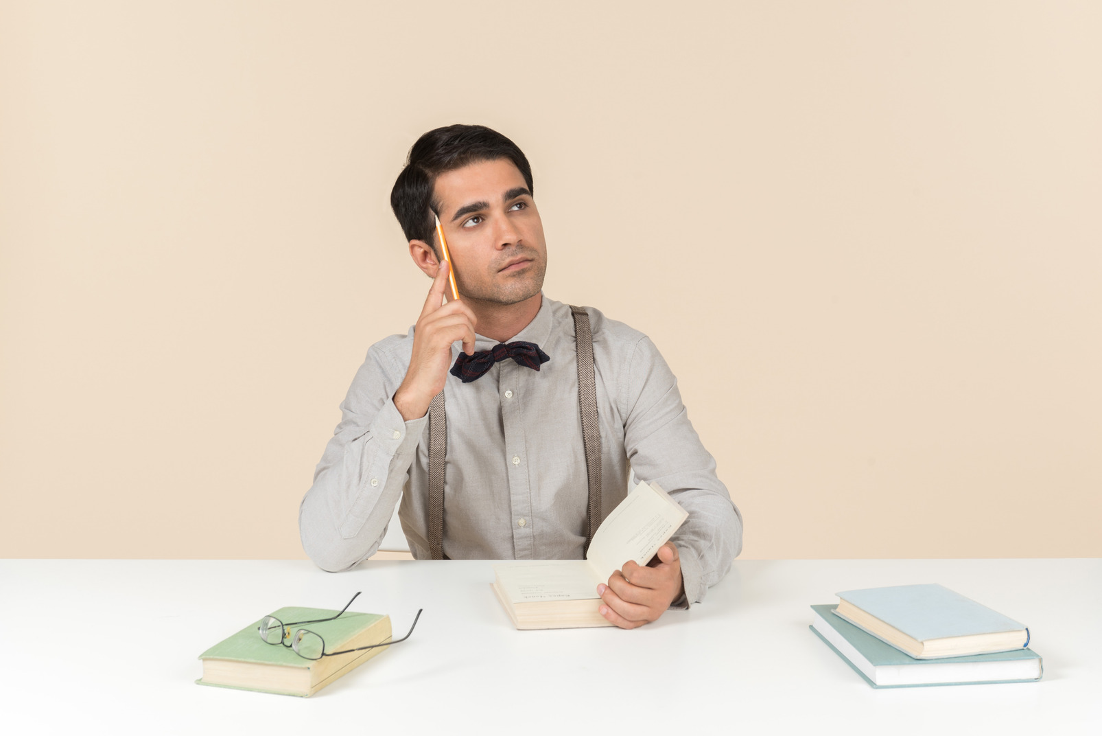 Pensive adult student sitting at the table with opened book