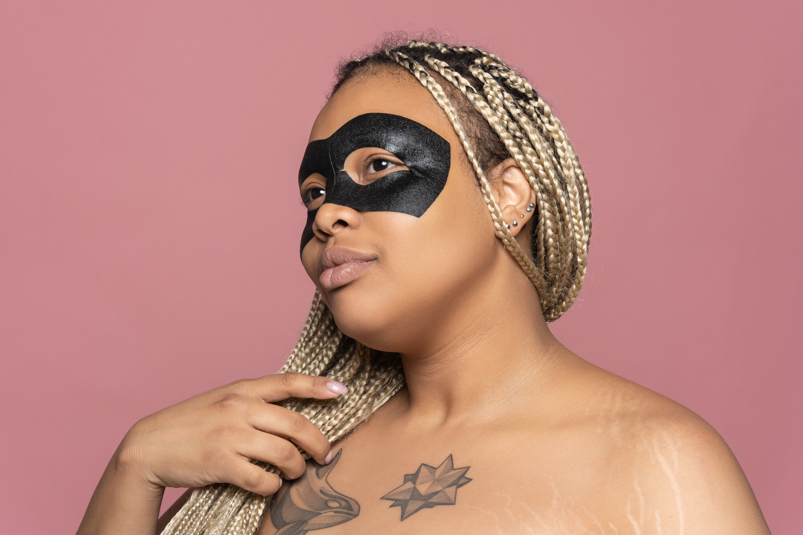 Black woman in eye mask looking at transparent mirror