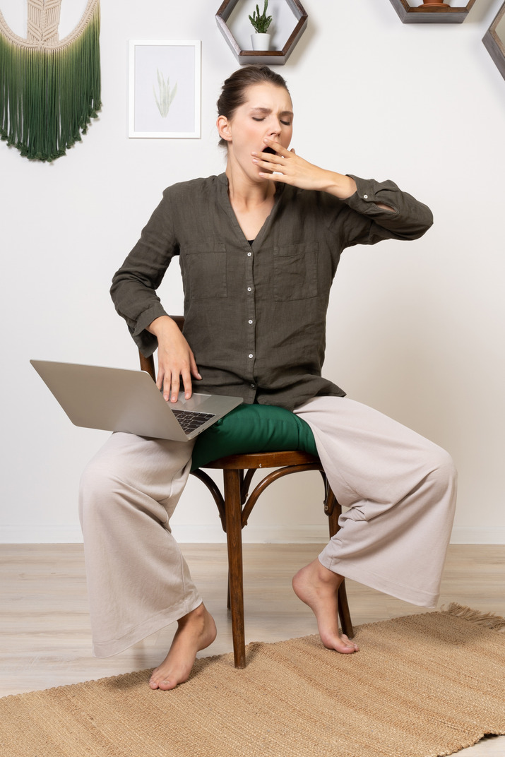 Front view of a tired young woman wearing home clothes sitting on a chair with a laptop