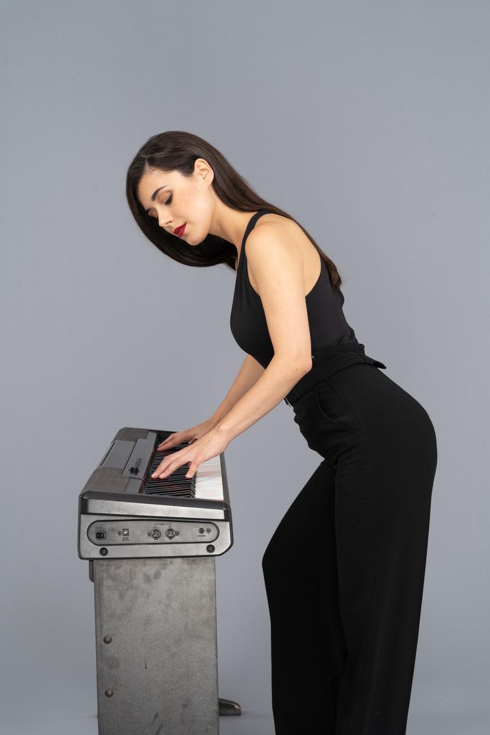 Seitenansicht einer jungen dame im schwarzen anzug, die klavier spielt