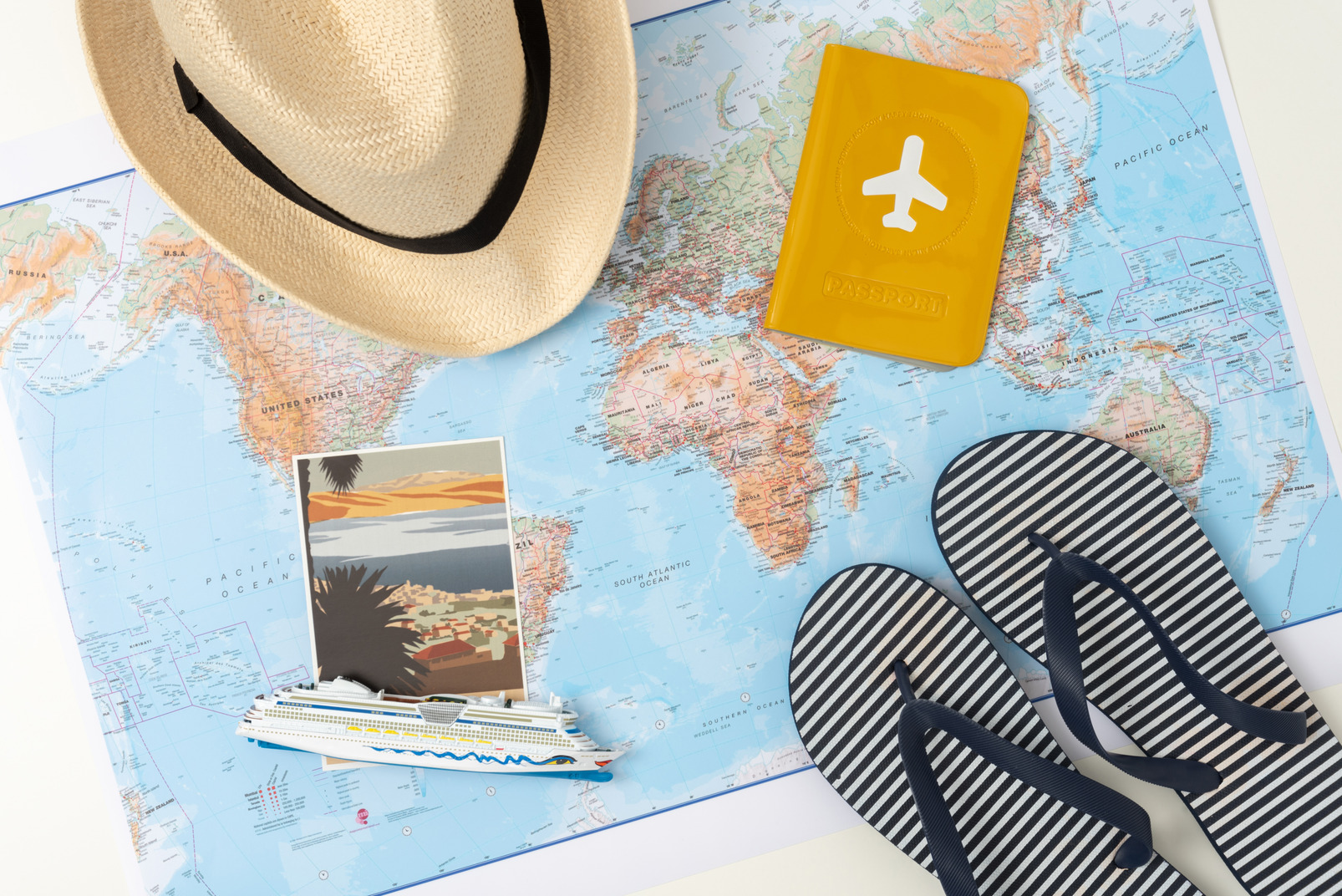 A straw hat and flip-flops, along with a passport and a picture of a nice place with palm trees and mountains, lying on the world map on my work desk as a subtle indicator of my desire to get a vacation