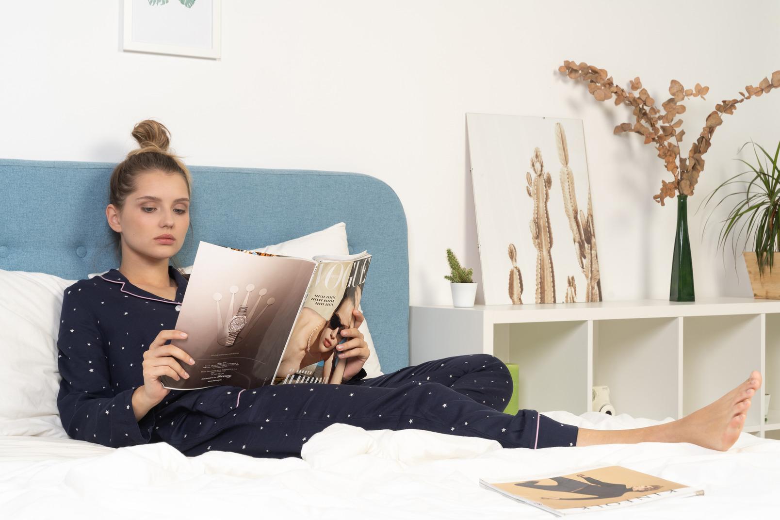 De cuerpo entero de una mujer joven en pijama acostado en la cama mientras lee una revista de moda