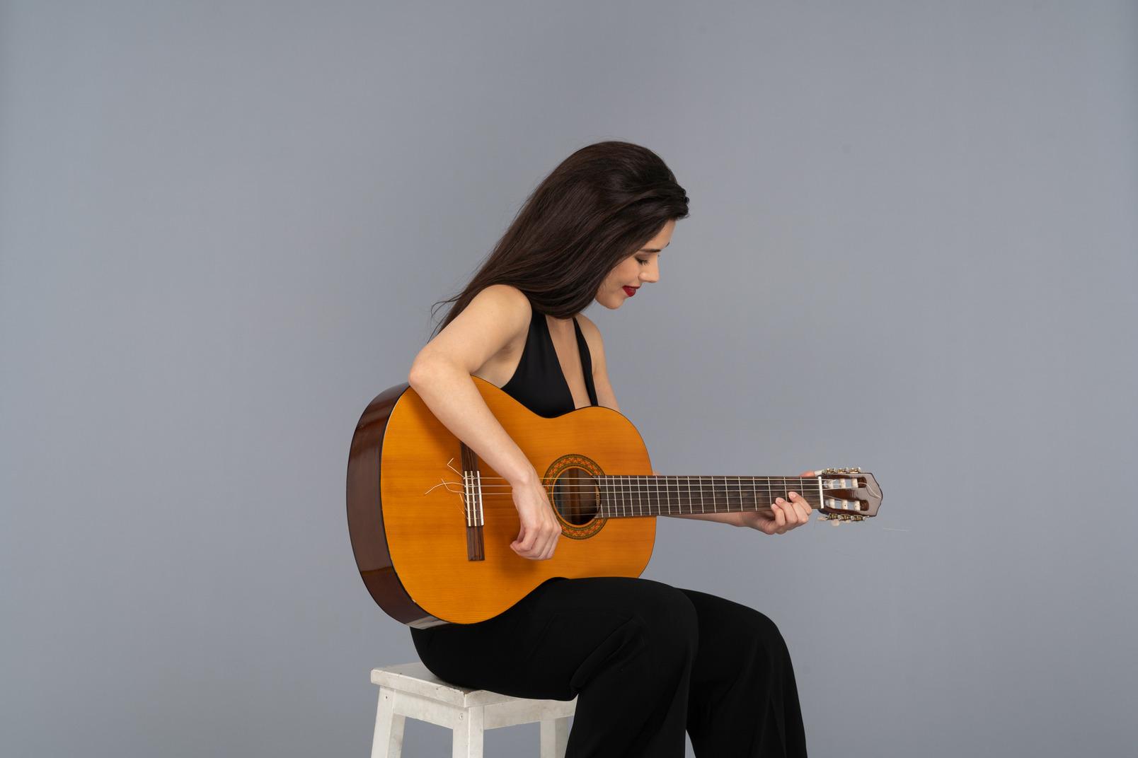 Dreiviertelansicht einer sitzenden jungen dame im schwarzen anzug, die gitarre spielt und nach unten schaut