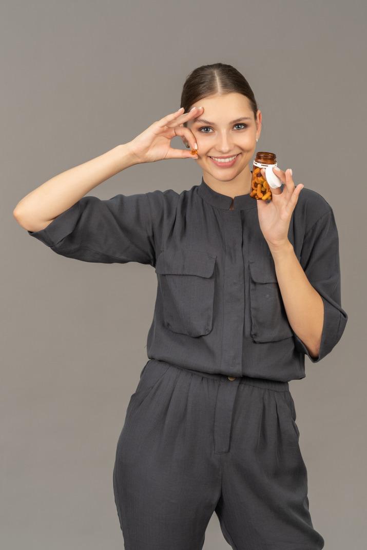 Vue de face d'une jeune femme en combinaison prenant des pilules dans un bocal