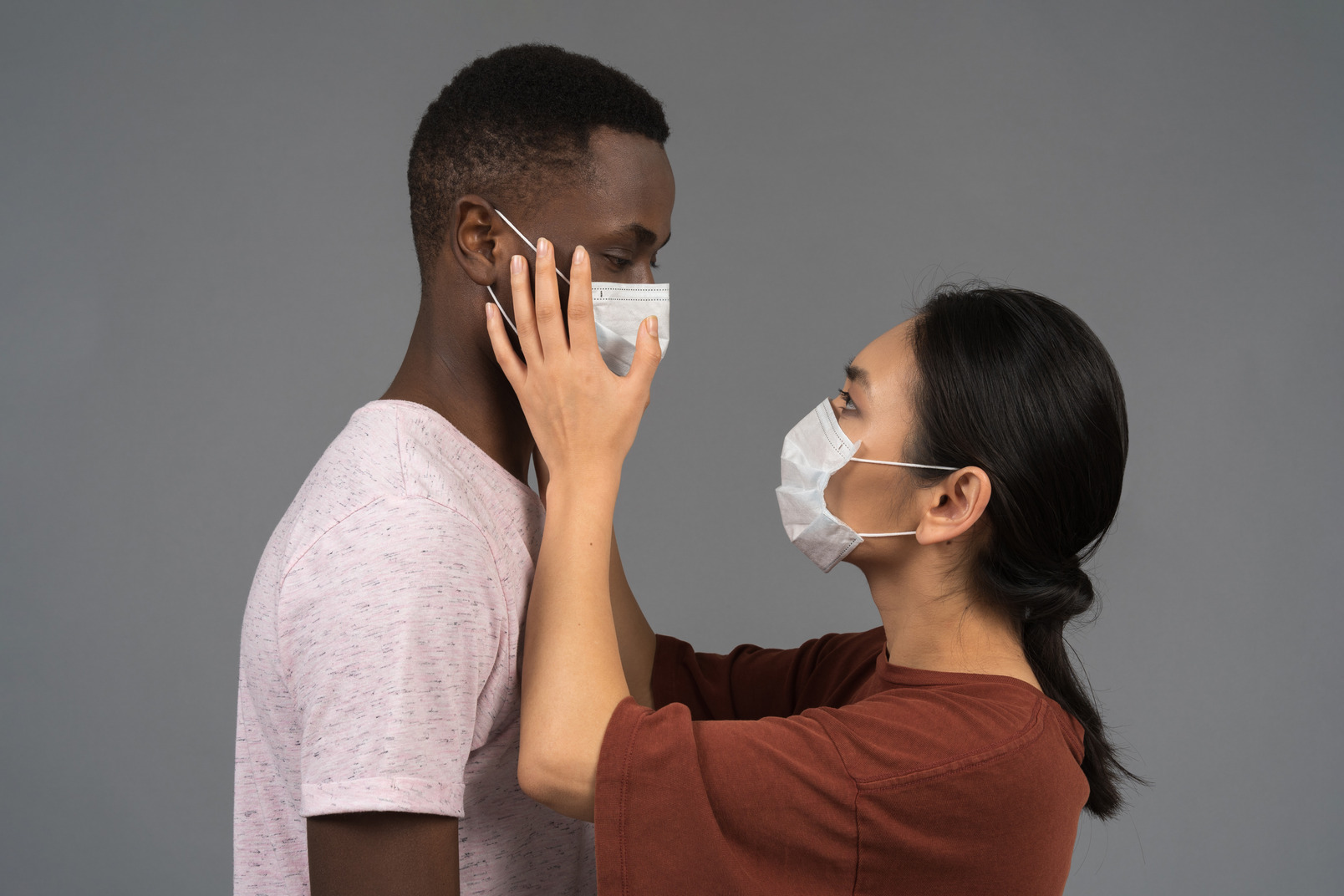 A young couple wearing face masks