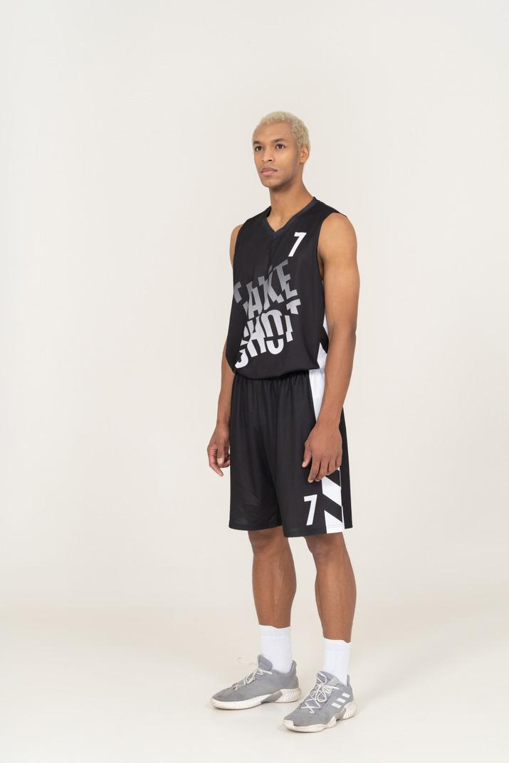 Vista de tres cuartos de un joven jugador de baloncesto masculino parado