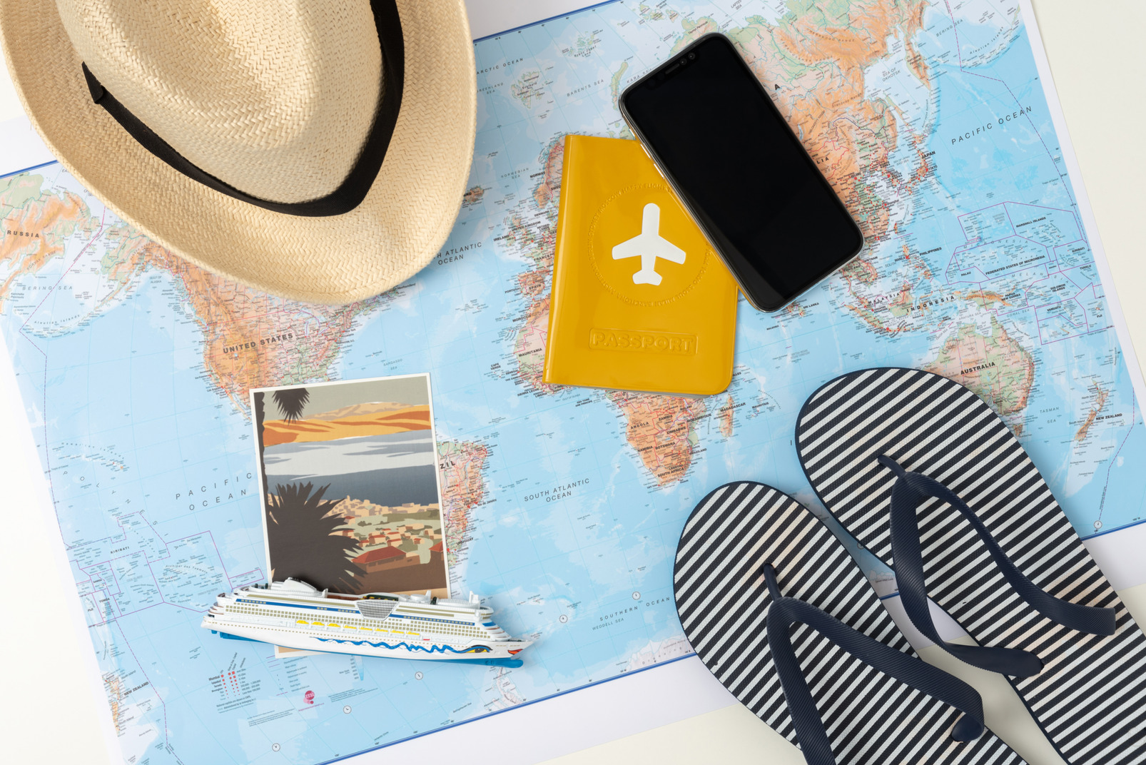 A passport, tiny ship model, flip-flops and a straw hat, all laid out beautifully over the world map, because i'm not just a tourist, but a designer