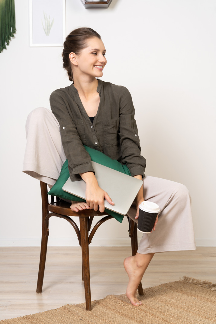 Front view of a smiling young woman sitting on a chair and holding her laptop & coffee cup