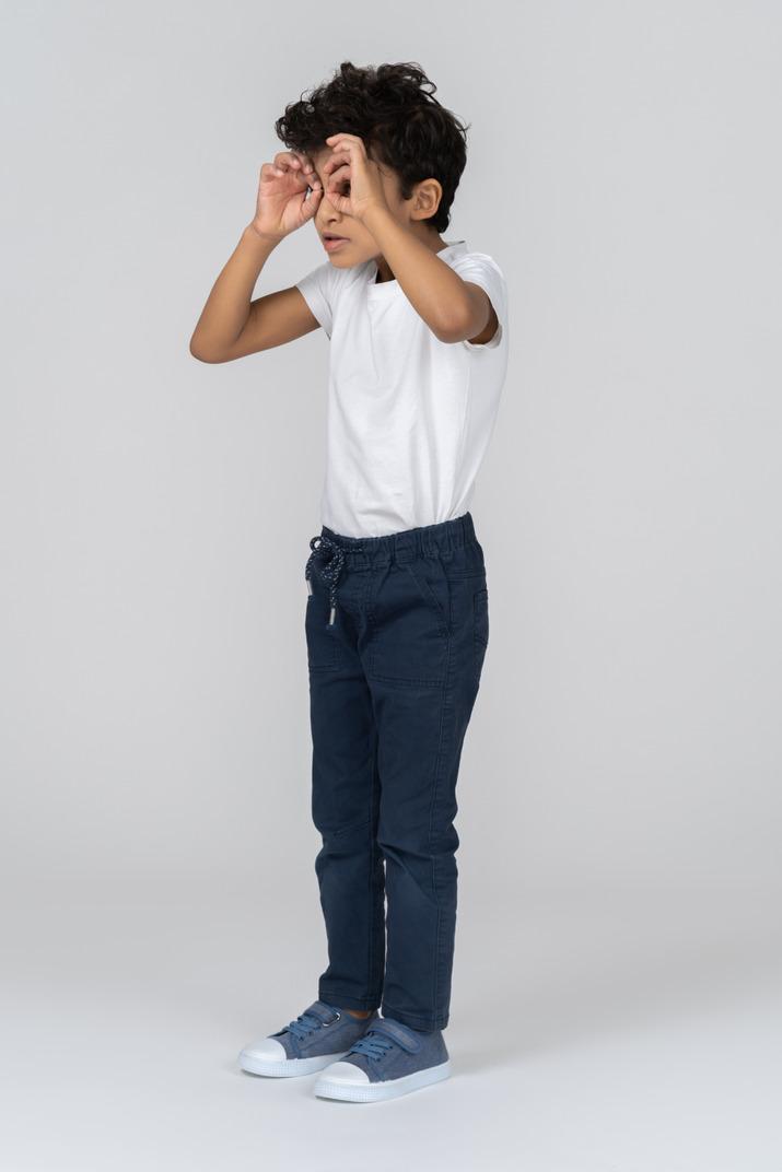 A boy looking through imaginable binoculars