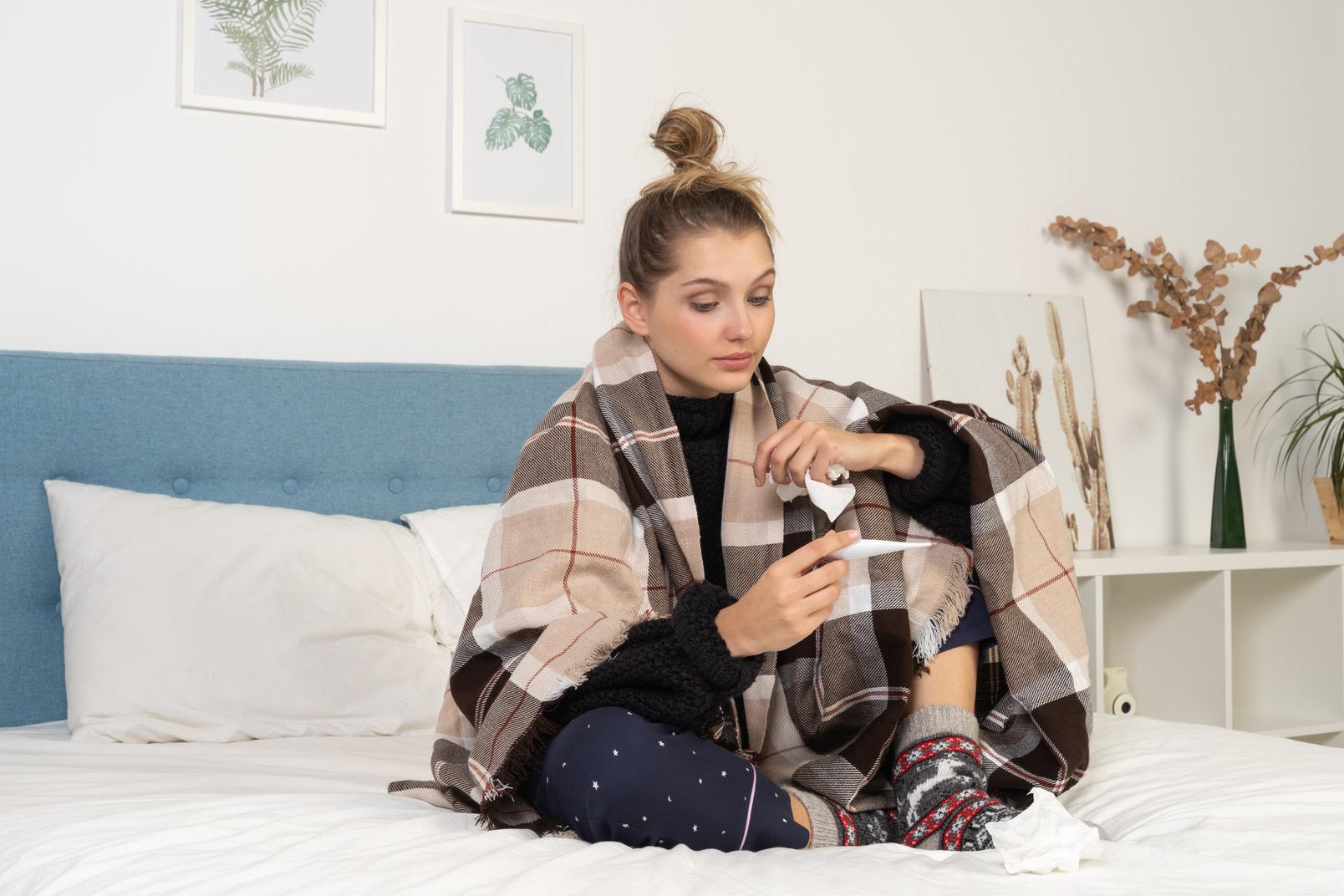 Vista frontal de uma jovem doente de pijama, enrolada em um cobertor xadrez, verificando sua temperatura