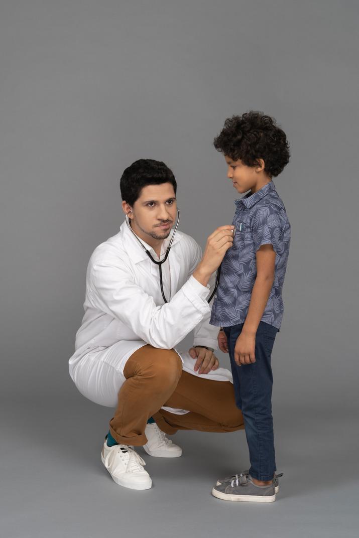 Doctor examining little child