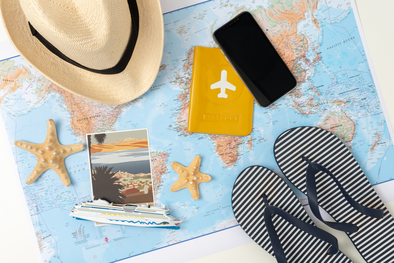 Striped flip-flops, straw hat, an international passport, smartphone and some souvenirs from the latest journey all brought together to create that summer vacation vibe you can feel already