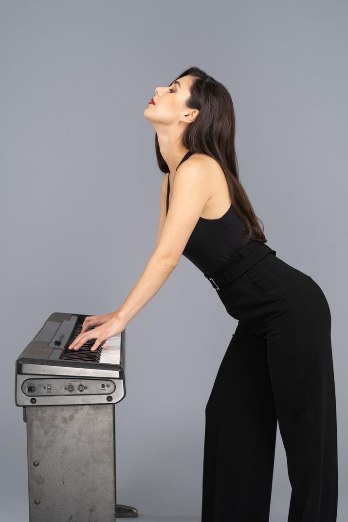 Vista lateral de una joven en traje negro tocando el piano mientras levanta la cabeza