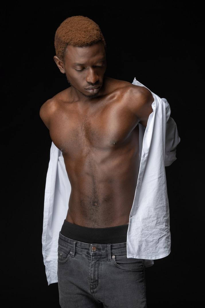 Nahaufnahme junger afrikanischer mann, der ein hemd anpasst