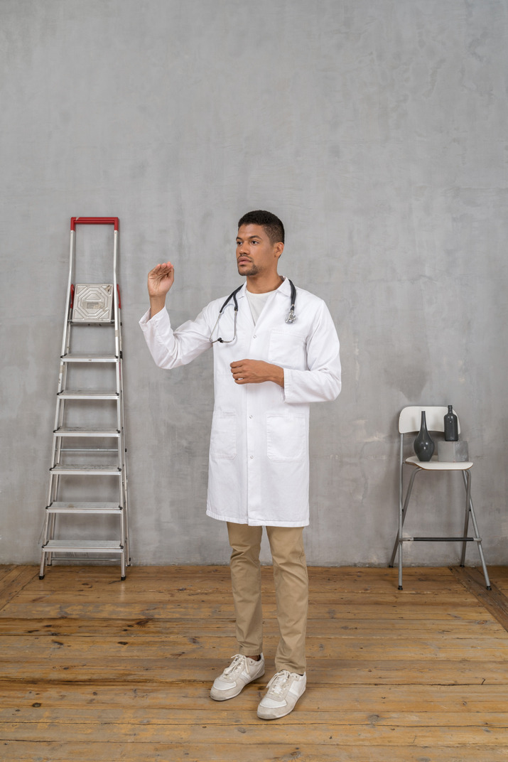 Three-quarter view of a young doctor standing in a room with ladder and chair showing a size of something