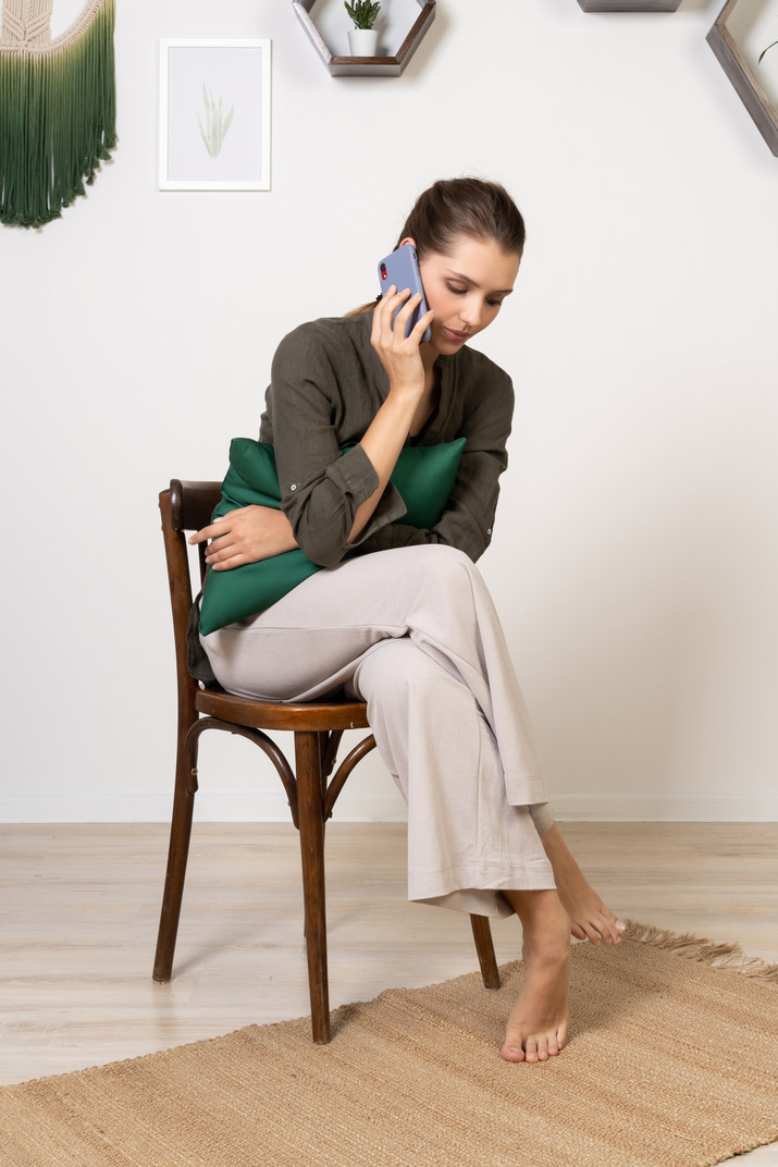Front view of a young woman sitting on a chair while having a phone call