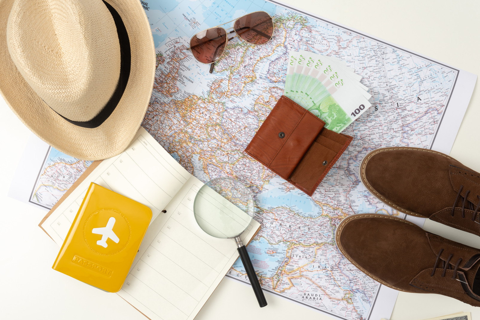 Only necessary things for a travel: a straw hat, comfortable boots, smartphone, sunglasses, passport and money