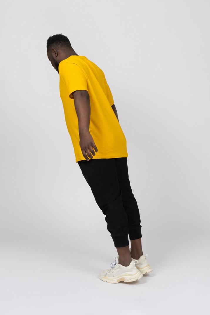 Vue de trois quarts arrière d'un jeune homme à la peau foncée en t-shirt jaune penché en avant et bras tendu