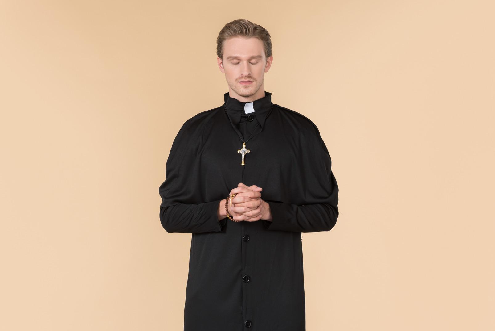 Catholic priest praying using prayer beads