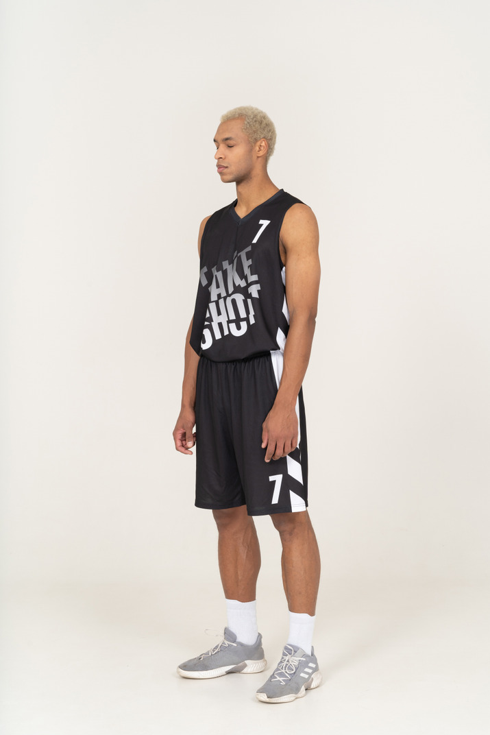 Three-quarter view of a young male basketball player standing with his eyes closed