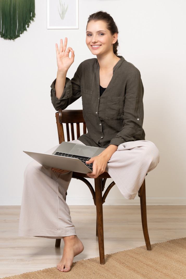 Front view of a smiling young woman sitting on a chair with a laptop & showing ok gesture