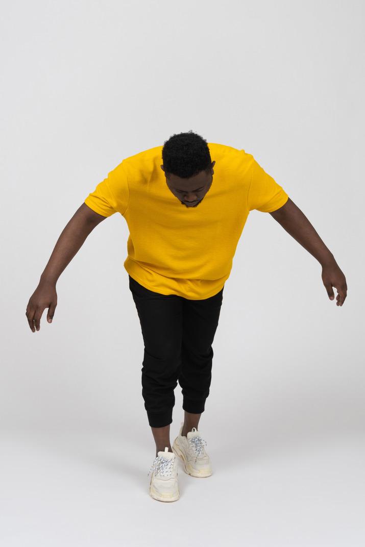 Vue de face d'un jeune homme à la peau foncée en t-shirt jaune penché en avant et bras tendu