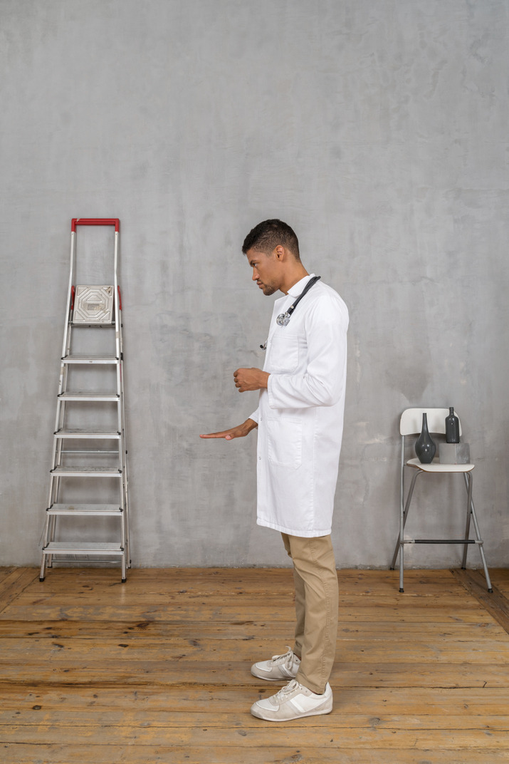 Side view of a young doctor standing in a room with ladder and chair showing a size of something