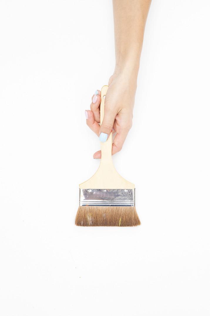 Female hand holding paint brush
