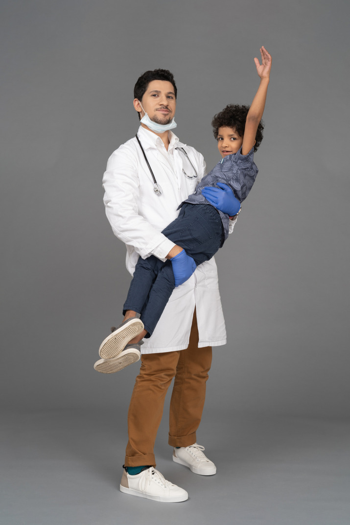 Doctor holding a happy boy