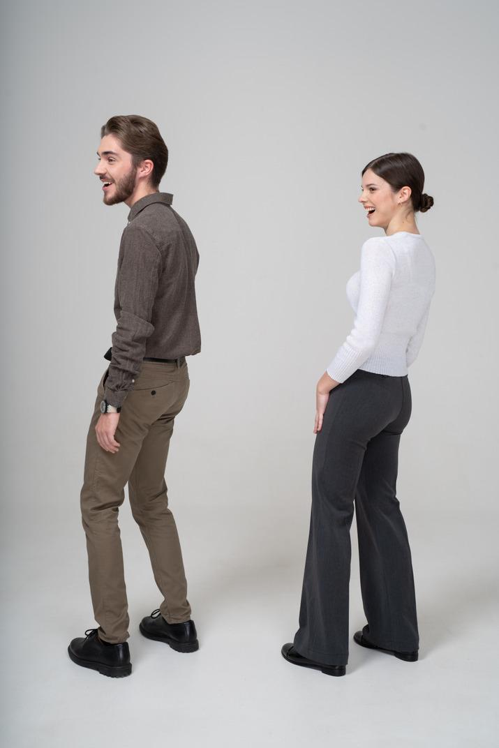 Seitenansicht eines lachenden jungen paares in bürokleidung