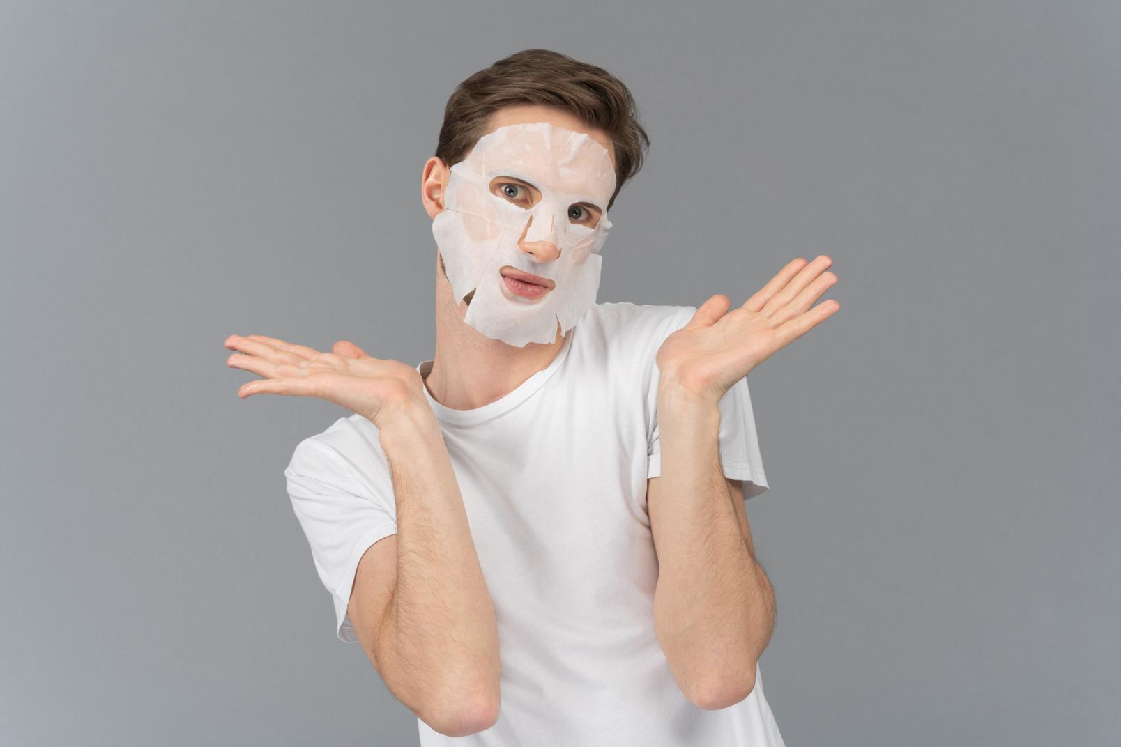 顔のマスクでポーズをとる若い男の正面図